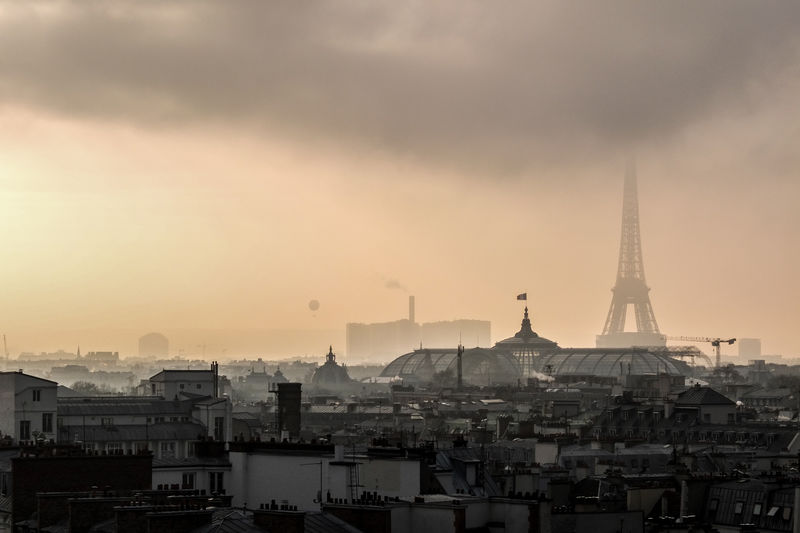 Eiffel tower in cityscape against sky during sunset