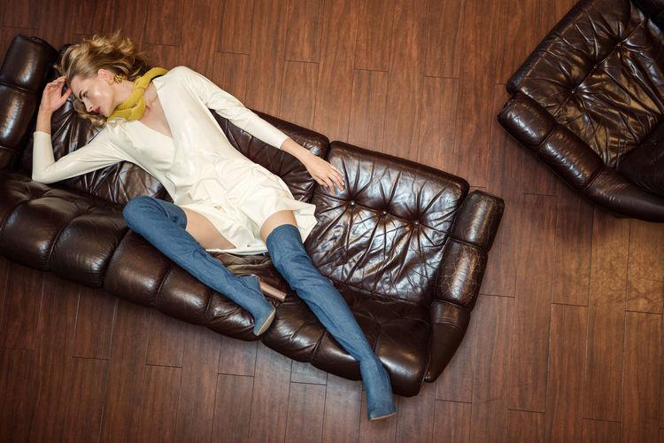 High angle view of woman lying down on hardwood floor