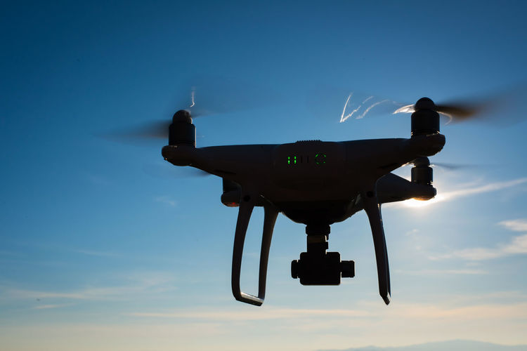 Low angle view of drone against blue sky