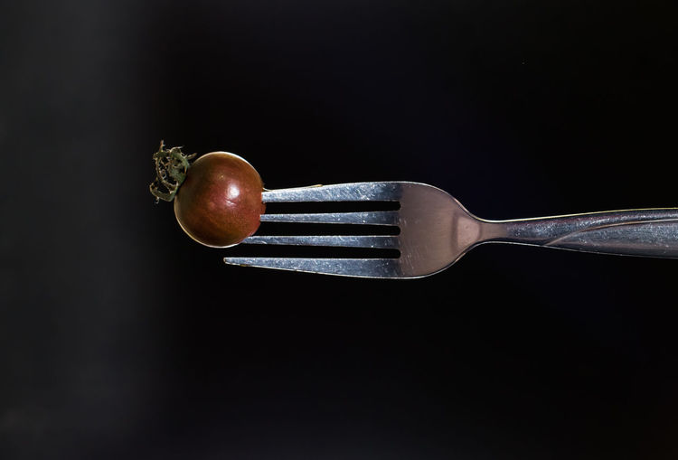 Small kumato tomato on fork isolated on the black background. Black Background Close-up Decor Food Food And Drink Fork Freshness Healthy Eating Indoors  Kitchen Utensil Kitchen Utensils Kumato Tomato No People Photo For Kitchen Interior Restaurant Decor Restaurant Interior Design Studio Shot Tomato Vegetable
