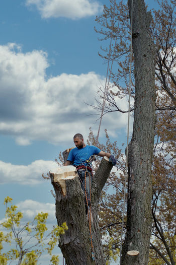 Man by tree trunk against sky
