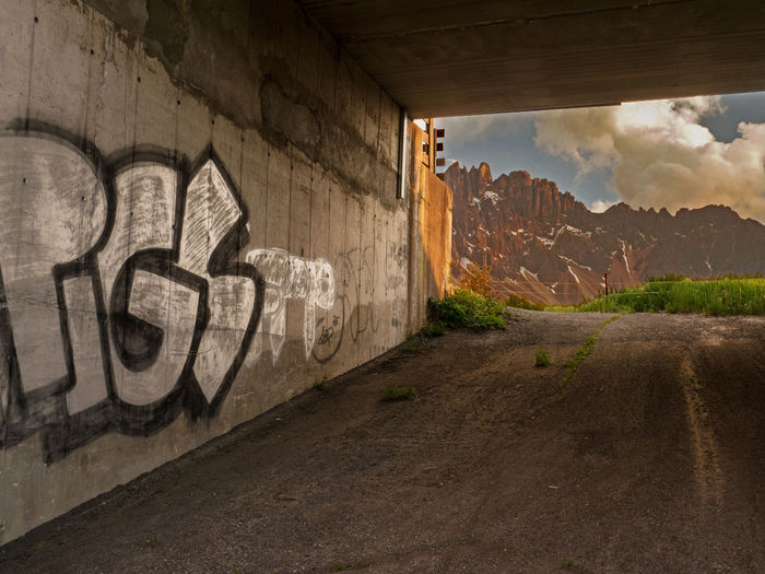 a graffity in opposite to the great dolomite panorama Alpen Alpes Bridge - Man Made Structure Built Structure Clouds And Sky Day Different Is Better . ❤ Different Points Of View Dolomites Dolomites, Italy Graffiti Mountains No People Nova Levante Outdoors Social Issues Spray Paint Streetphotography Summer Evening Summer Views Südtirol Welschnofen Break The Mold Art Is Everywhere