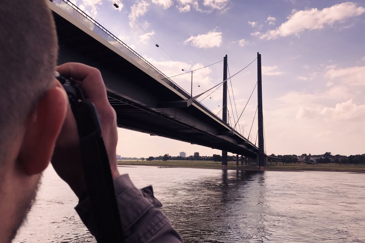 bridge - man made structure, connection, sky, real people, river, one person, architecture, lifestyles, men, water, transportation, outdoors, cloud - sky, built structure, suspension bridge, day, human hand, nature, city, people