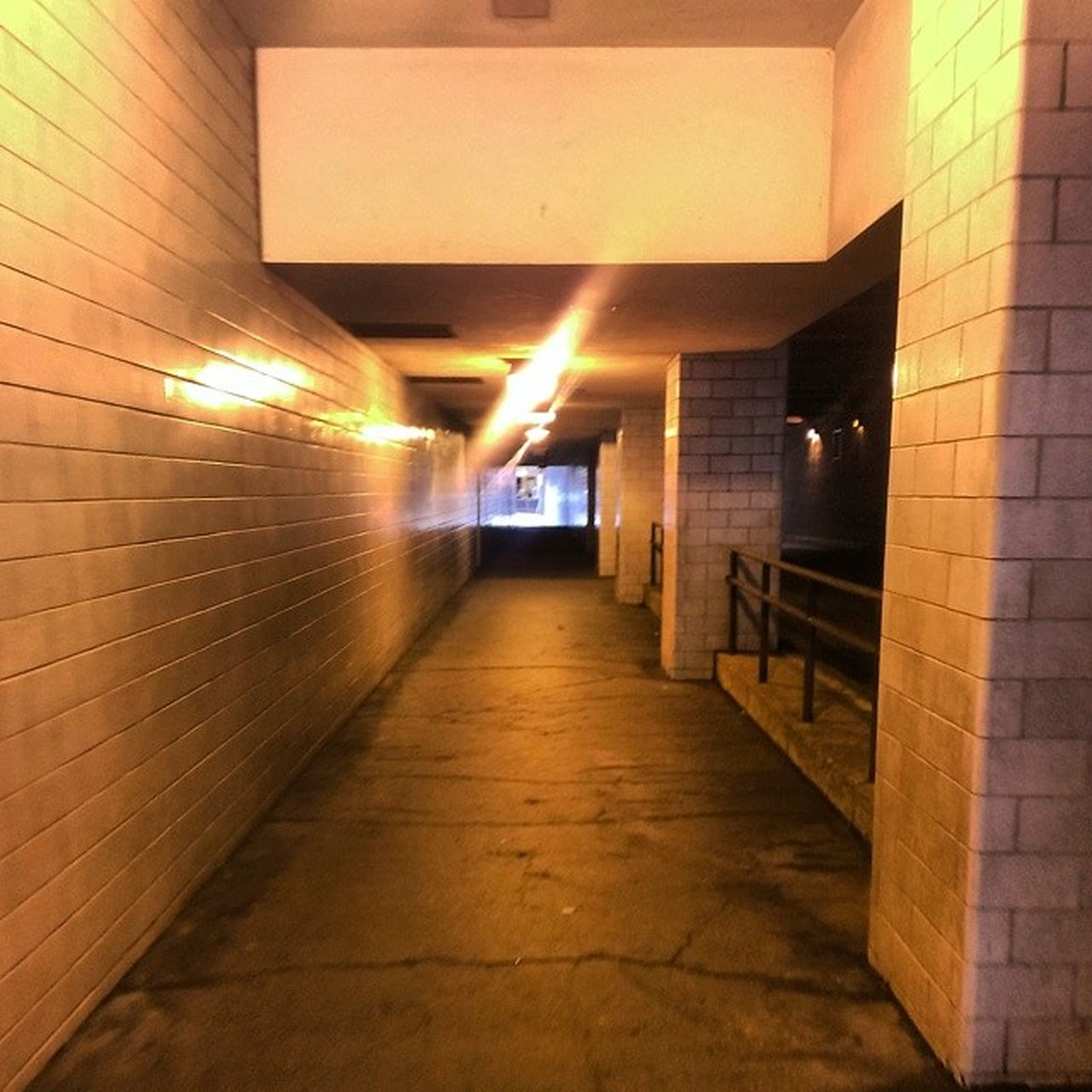 architecture, illuminated, built structure, the way forward, building exterior, lighting equipment, night, corridor, building, diminishing perspective, indoors, empty, wall - building feature, city, light - natural phenomenon, vanishing point, narrow, no people, flooring, absence