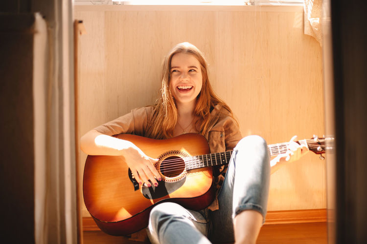 Portrait of a smiling young woman playing guitar