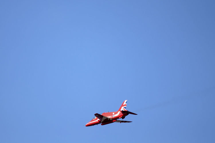 Aerospace Industry Air Vehicle Airplane Blue Clear Sky Copy Space Day Fighter Plane Flying Low Angle View Mid-air Mode Of Transportation Motion Nature No People on the move Outdoors Plane Red Red Arrows Sky Transportation