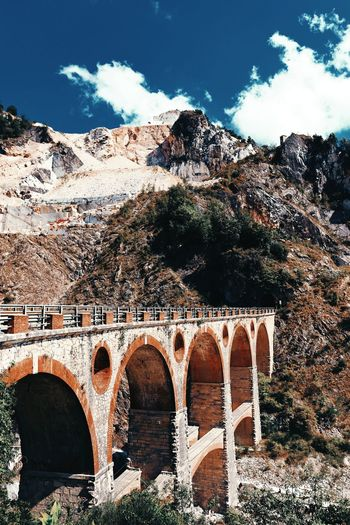Arch bridge over mountain against sky