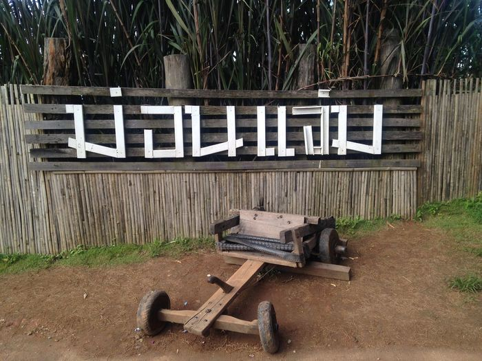 Monjam Architecture Bench Capital Letter Communication Day Front Or Back Yard Grass Hand Saw Information Information Sign Land Nature No People Outdoors Plant Sign Text Tree Western Script Wood Wood - Material
