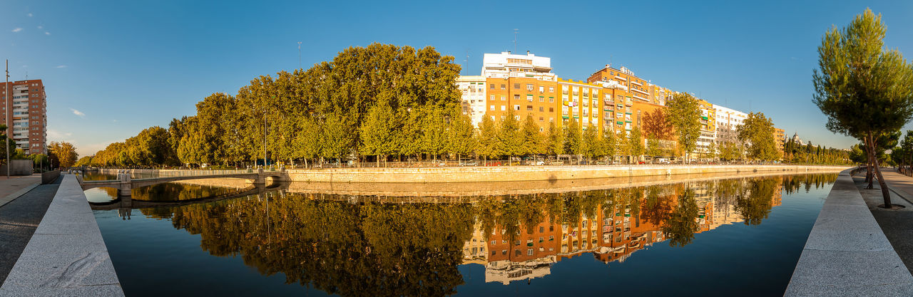 River view at Madrid Apartments Architecture Buidings Building Exterior Built Structure Calm City Cityscape Clear Sky Day Manzanares No People Outdoors Panoramic Quiet Reflection River Riverfront Sky Street Travel Destinations Tree Urban Warm Clothing Water