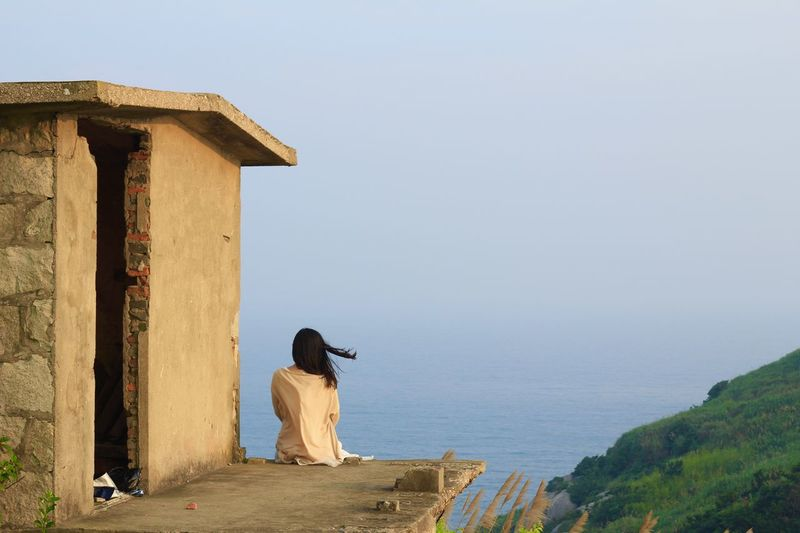 Rear View Of Woman Sitting On Rooftop And Looking At View