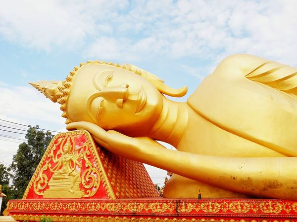 Big golden buddha statue sleeping near Pha That Luang temple at Vientienne, Laos. Landmark and famous place for tourist and visit in Vientienne, Laos. Ancient Respect Art And Craft Big Buddha Statue Buddhism Cloud - Sky Gold Colored Hand Headshot Landmark Loas Low Angle View Object Outdoors Place Of Worship Religion Sculpture Sleeping Spirituality Statue Temple