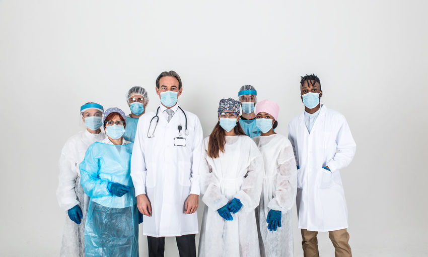 Portrait of doctors wearing mask standing against white background