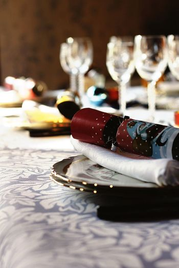 Close-Up Of Christmas Cracker On Plate At Table