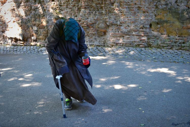 Homeless person walking on road