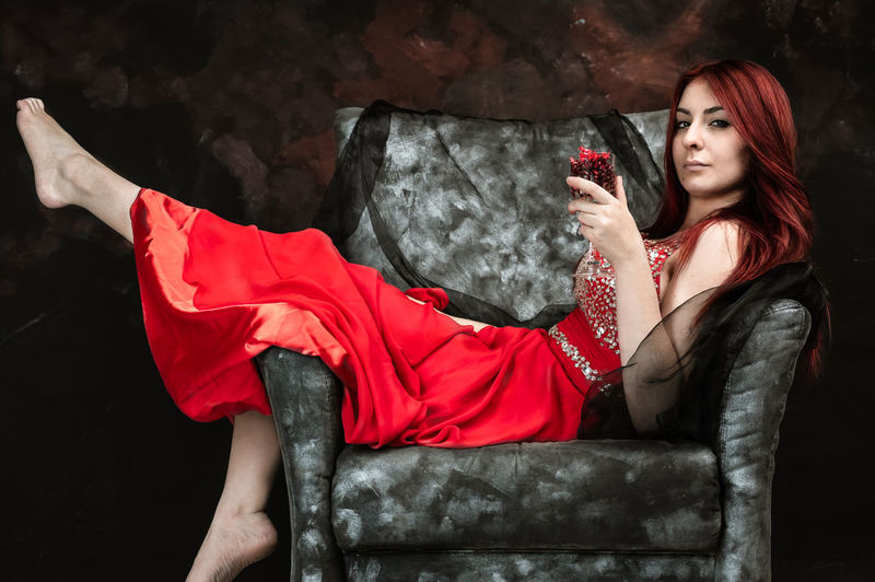 portrait of a red head woman in red dress The Portraitist - 2019 EyeEm Awards Young Women Red Portrait Beauty Females Sitting Women Black Background Human Face Christmas Present Fashion Model Haute Couture Posing Society Beauty Cocktail Dress Eye Make-up