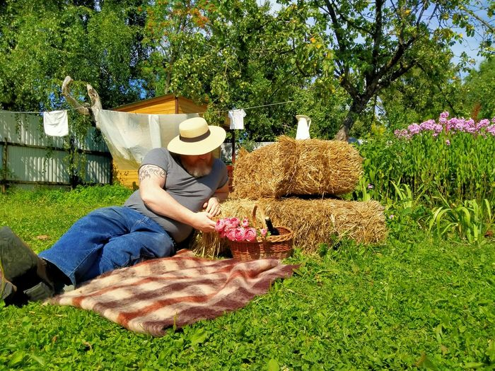 Midsection of woman sitting by potted plant on field