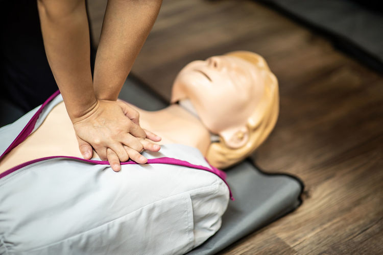 High angle view of person showing cpr over dummy on floor