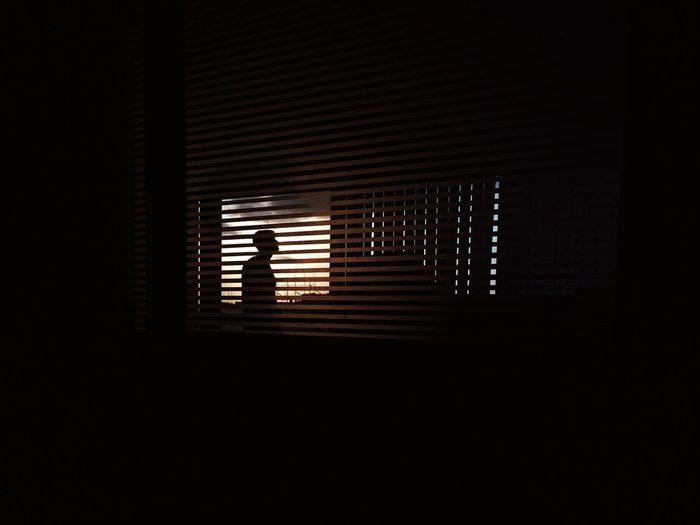 Silhouette man seen through blinds window