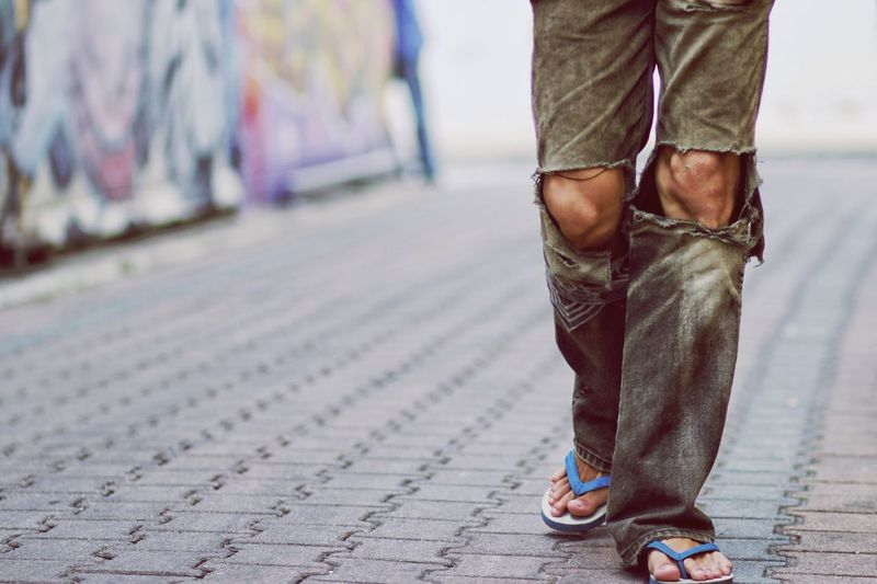 Low Section Of Man In Torn Pants Walking On Street