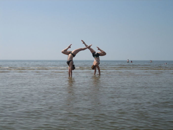 Friends Doing Handstand In Sea Against Clear Sky