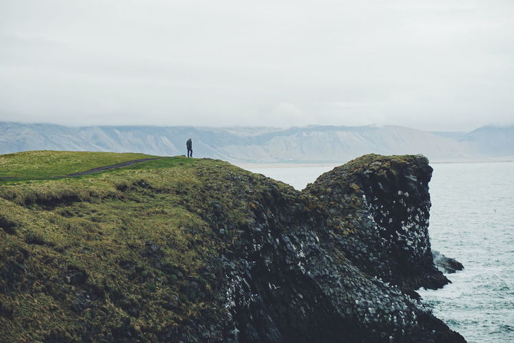 Man standing on cliff by lake against cloudy sky at snaefellsnes peninsula
