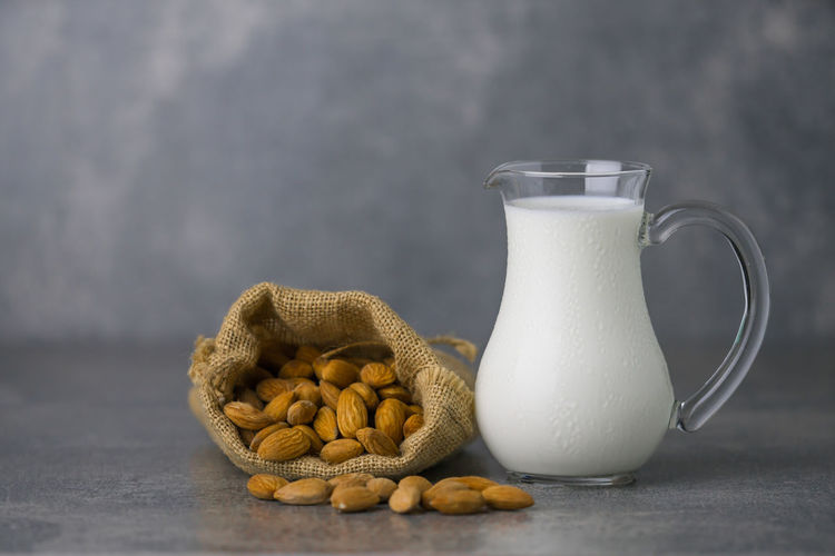 almond milk in jar with almonds in sackcloth on concrete background Juice Liquid Raw Seed Vegetarian Almond Drink Healthy Eating Jar Milk Nut Nutrition Organic Product Protien Sackcloth Vegan