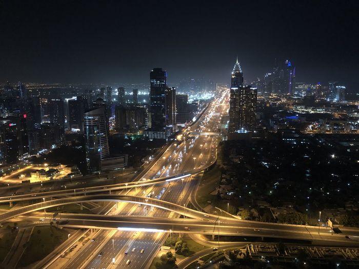 High angle view of illuminated city buildings at night. - sheikh zayed road dubai
