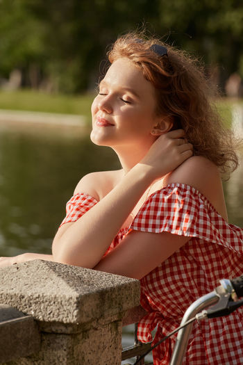 Side view of smiling young woman looking away outdoors