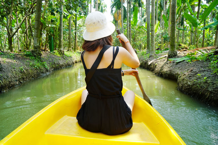 Rear view of woman wearing hat by lake in forest