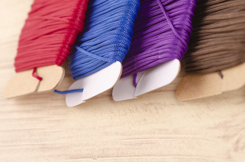colorful stacking cotton yarn wool on wooden background. Close-up Multi Colored Textile Indoors  Still Life No People Choice Variation Art And Craft Wood - Material Table In A Row Clothing Blue Thread Creativity Craft Side By Side Selective Focus High Angle View Purple