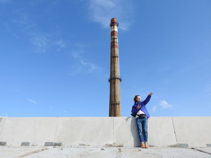 Low angle view of woman pointing while standing by lighthouse against sky