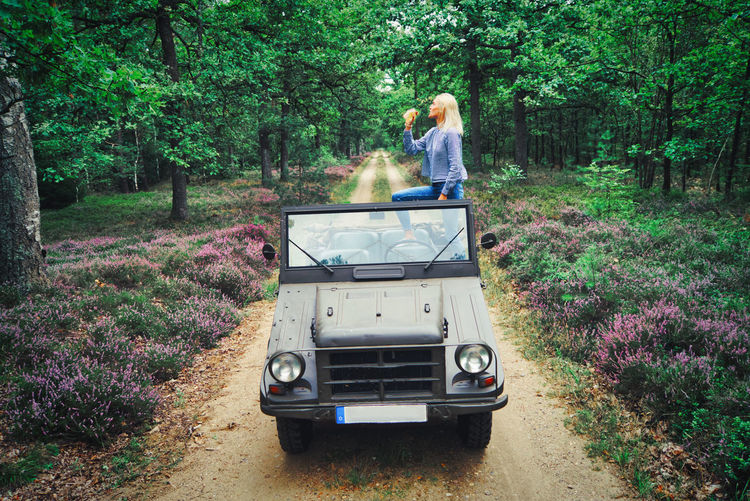 Woman holding bottle while standing in jeep at forest