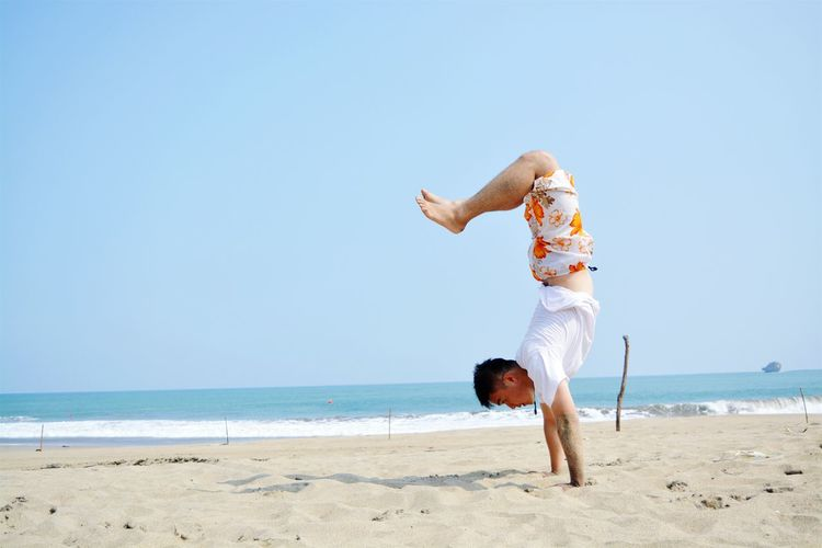 Side view of man doing handstand at beach against clear blue sky during sunny day