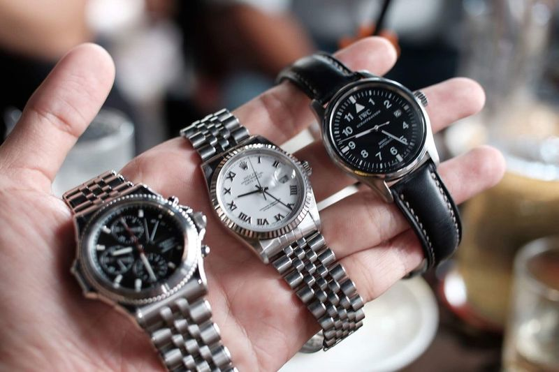 Close-up of human hand holding wristwatches