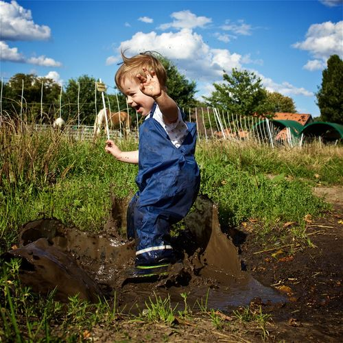 Full length of happy playful boy on muddy field