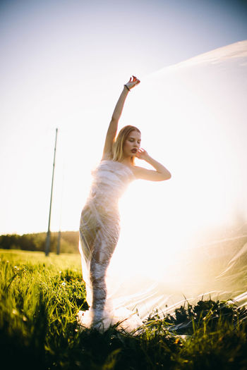 Human Arm Sky One Person Leisure Activity Arms Raised Full Length Sunlight Limb Grass Land Nature Plant Young Adult Field Happiness Women Emotion Casual Clothing Human Limb Lens Flare Outdoors Hairstyle