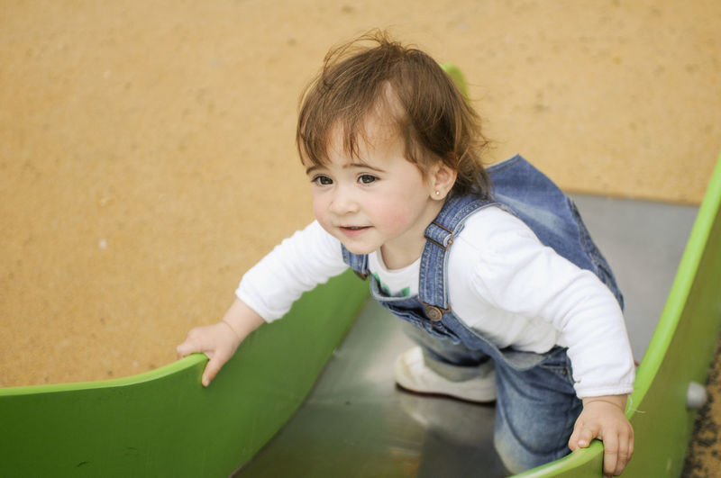 High angle view of cute baby girl on slide at park