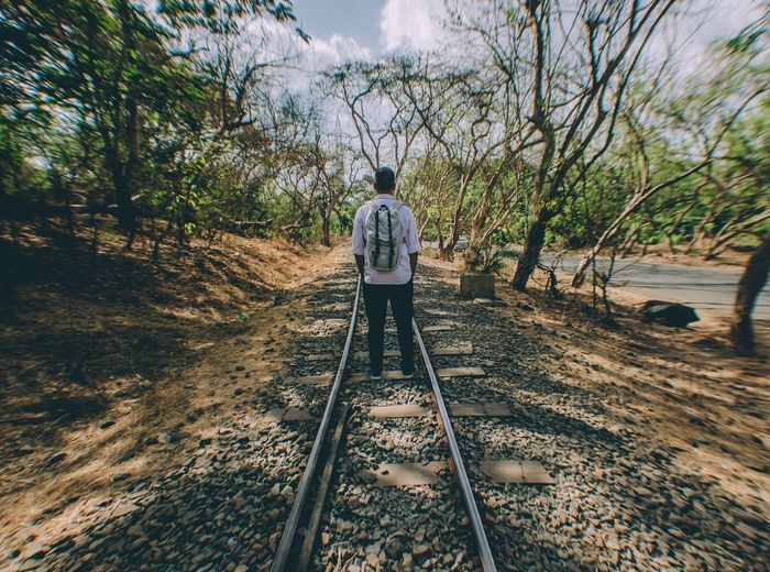 Rear view of man standing on railroad track