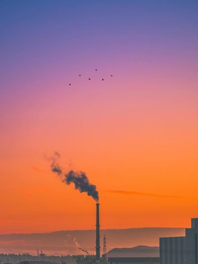 Silhouette smoke emitting from chimney against sky during sunset