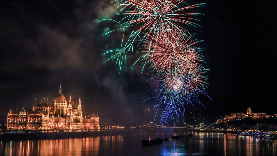Firework display by parliament building over danube river at night