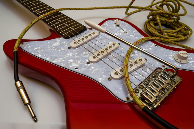 Red electric guitar and long vintage yellow jack cable to connect in an amplifier. Musical instrument with details and isolated on white background. Rock Amplifier Arts Culture And Entertainment Cable Cables Close-up Connection Electric Guitar Fretboard Guitar High Angle View Indoors  Music Musical Equipment Musical Instrument Musical Instrument String No People Red Setting Still Life String String Instrument Table Technology Vintage