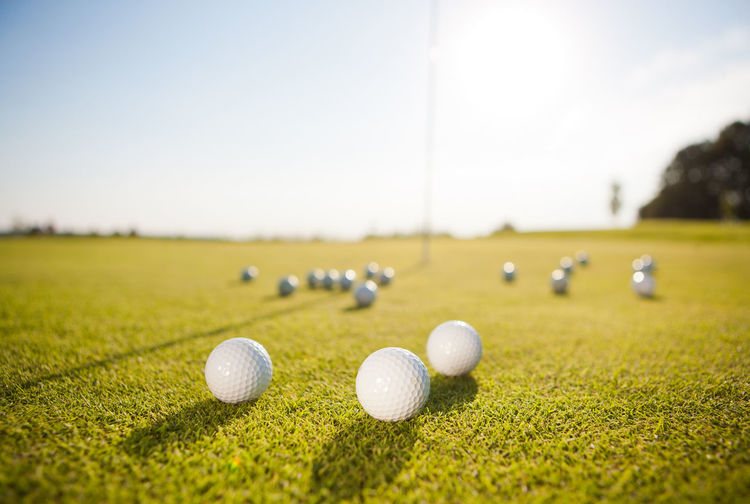 Close-Up Of Golf Balls On Grass Against Sky