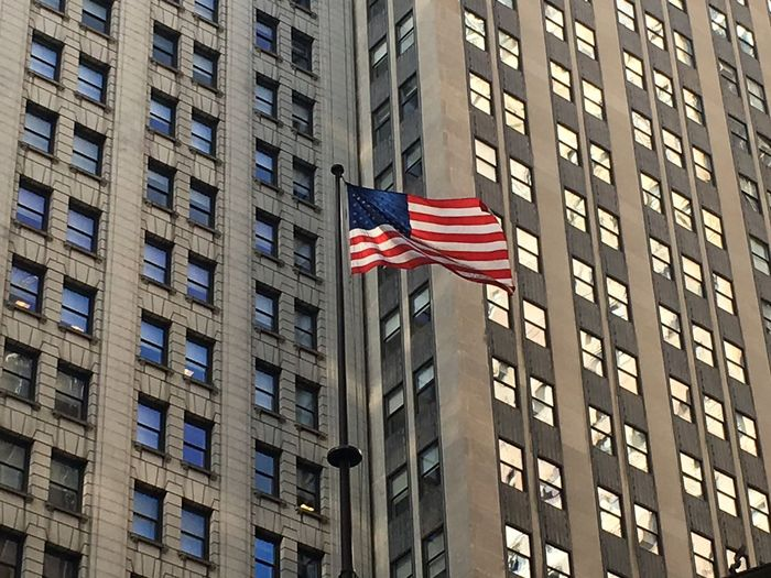 Low angle view of american flag 8against buildings