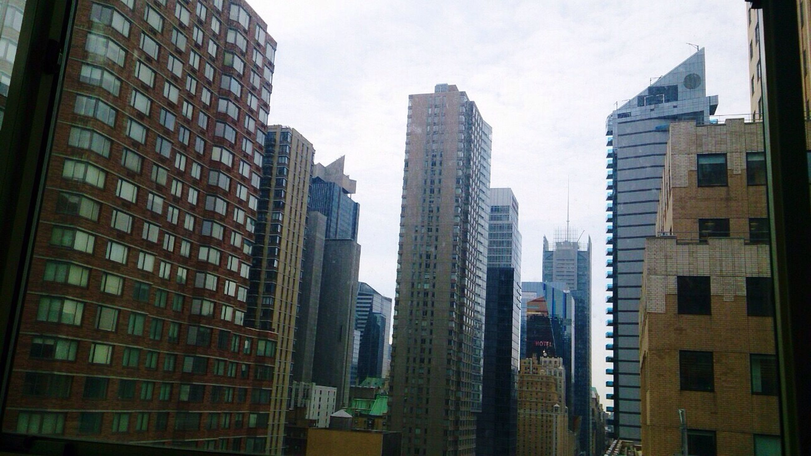 building exterior, architecture, built structure, city, skyscraper, office building, modern, tall - high, low angle view, building, tower, sky, glass - material, tall, window, city life, residential building, financial district, development, urban skyline