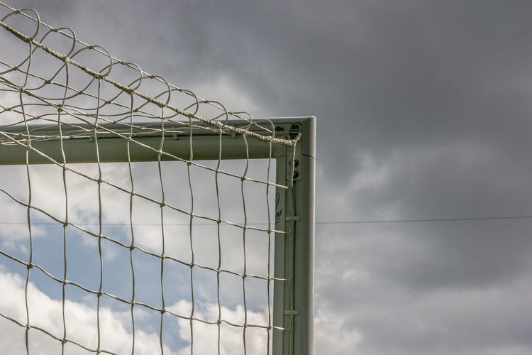 Low Angle View Of Net Against Cloudy Sky