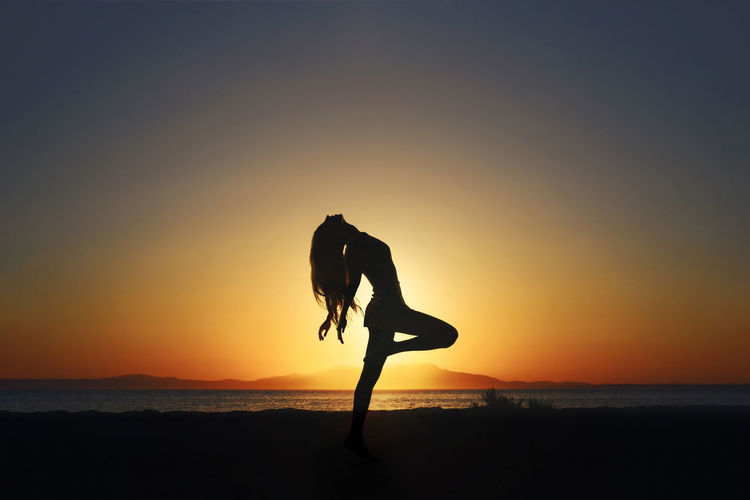 Silhouette of woman dancing at beach against sky during sunset