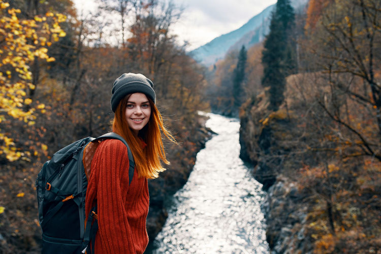 Smiling young woman in forest during autumn