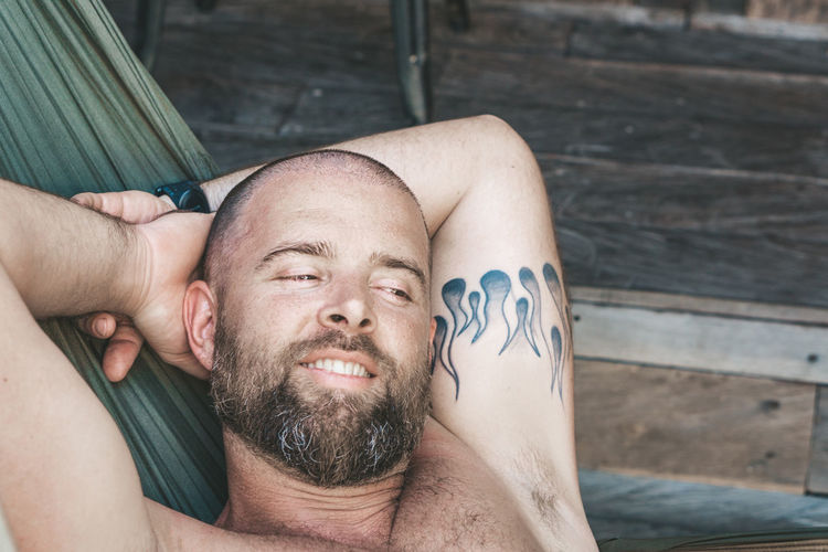 Relaxing in a hammock Headshot One Person Beard Men Portrait Facial Hair Real People Lifestyles Shirtless Leisure Activity Lying Down Males  Adult Tattoo Relaxation Young Adult Mature Adult Front View Mature Men Hands Behind Head Outdoors Human Arm