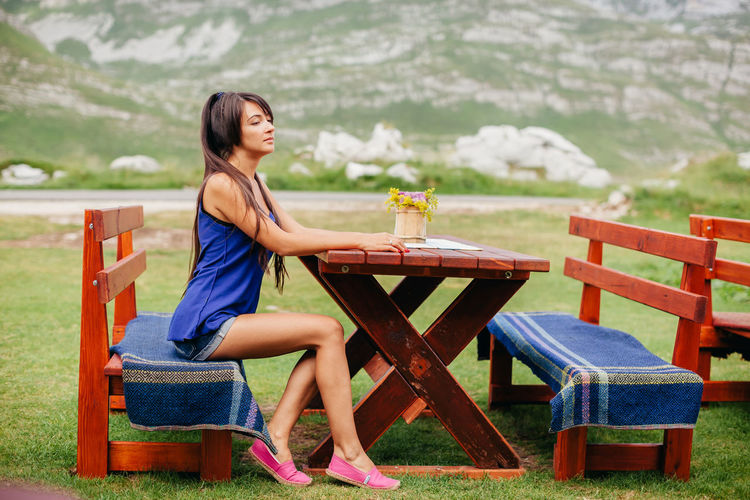 Side view of mid adult woman sitting on bench