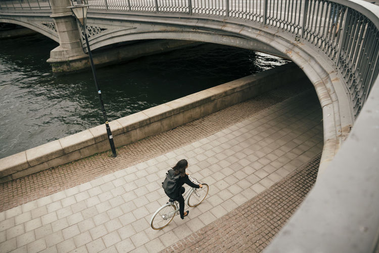 High angle view of woman riding bicycle on bridge over river